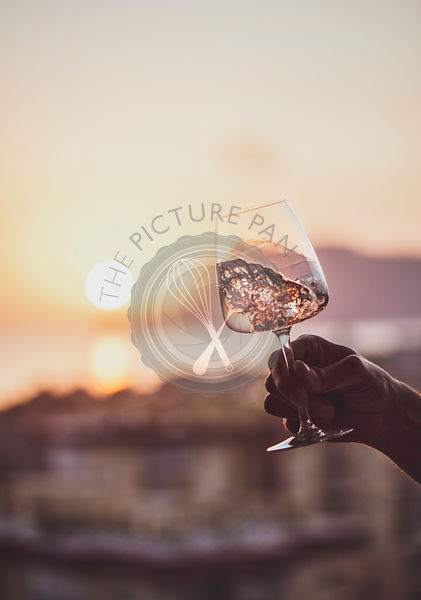 Man's hand holding rose wine with sea at background