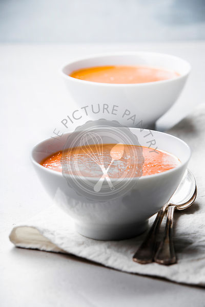 Homemade tomato cream soup in bowls  (or gazpacho) over concrete background