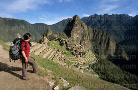 Tourist finishes the Inca Trail at Machu Picchu, Huayna Picchu peak in background, Peru
