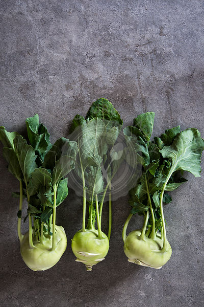 Fresh kohlrabi stems with leafs over grey concrete background