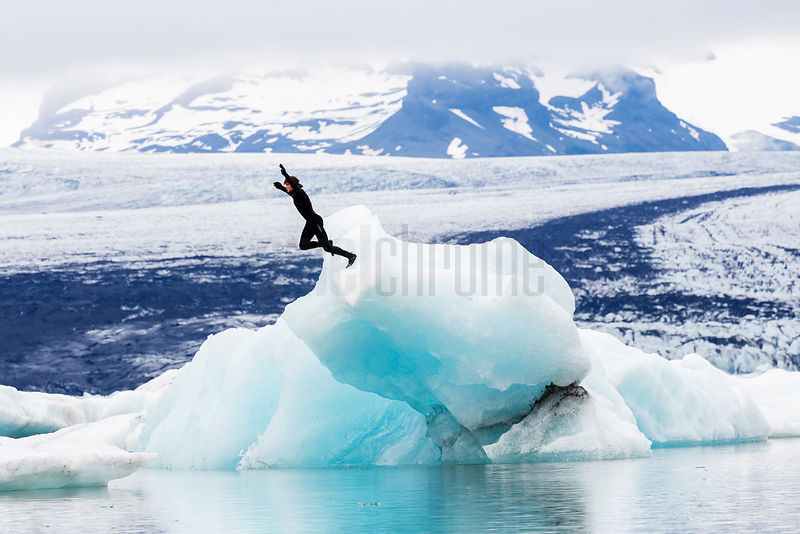 Surfer Jumping into Glacial Lagoon