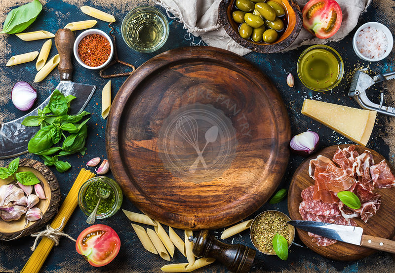 Italian food cooking ingredients on dark plywood background with round wooden tray in center