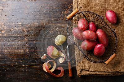Raw potato in metal basket and burlap bag on wooden background copy space