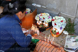 Devotee offering candles to skulls, Ñatitas festival, La Paz, Bolivia
