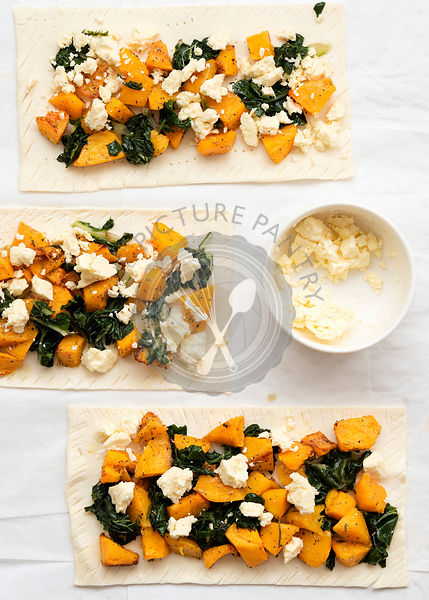 Three uncooked roast pumpkin, spinach and feta cheese tarts on baking paper.