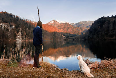 Austria, St. Gilgen, Krottensee in autumn, young man with dog