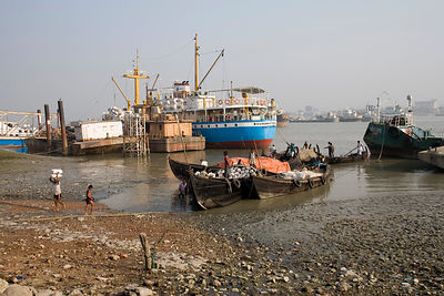 Bangladesh - Chittagong - Workers unload cargo from a ship to a waiting lorry in the docks at Sadarghat