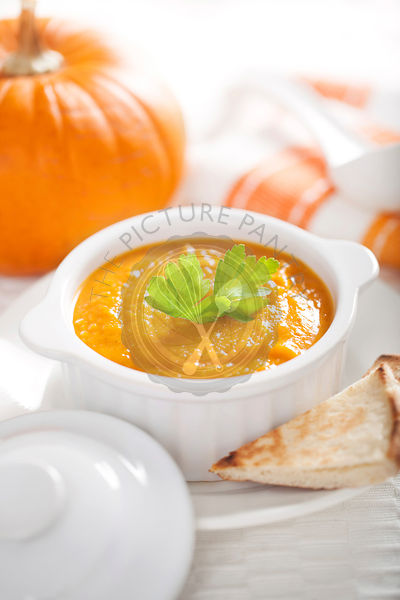 Pumpkin soup in a white bowl with pita bread