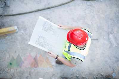 Construction worker reading plan at construction site
