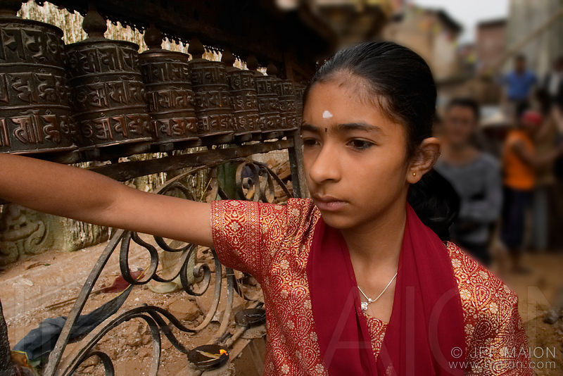 Young woman turning prayer wheels