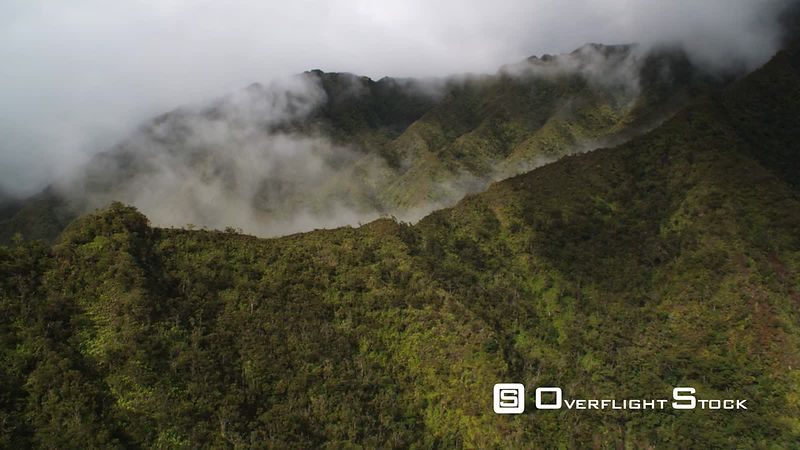 Flying over forested ridgeline to reveal mist-filled narrow canyon.