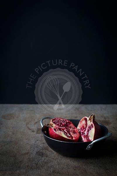 Pomegranate cut in halves in black bowl on wooden tabletop before black background