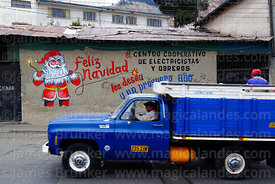 Vintage blue truck driving past Father Christmas mural on wall of the offices of an electricians and electrical workers cooperative, La Paz, Bolivia