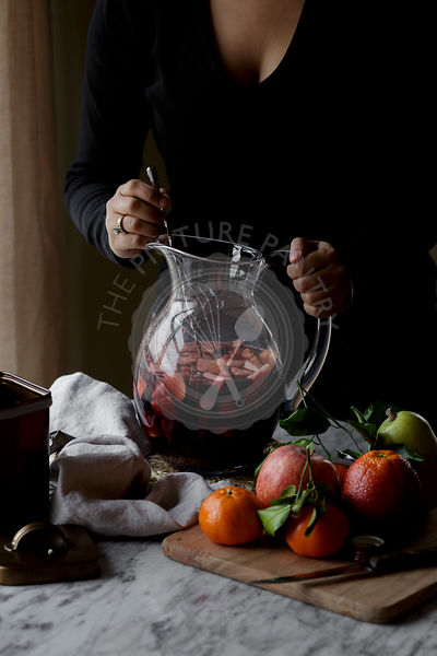 A woman making homemade Sangria