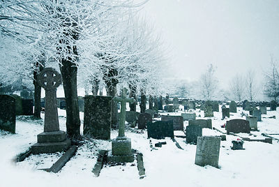An atmospheric image of tombstones in a old, snow covered church graveyard.