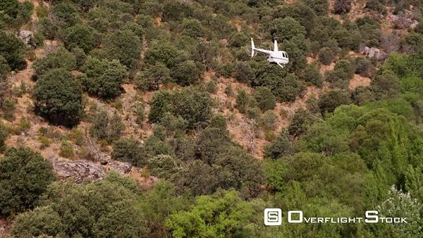 WS helicopter in slow flight over rugged arid hills, rear airtoair view, RED R3D 4K