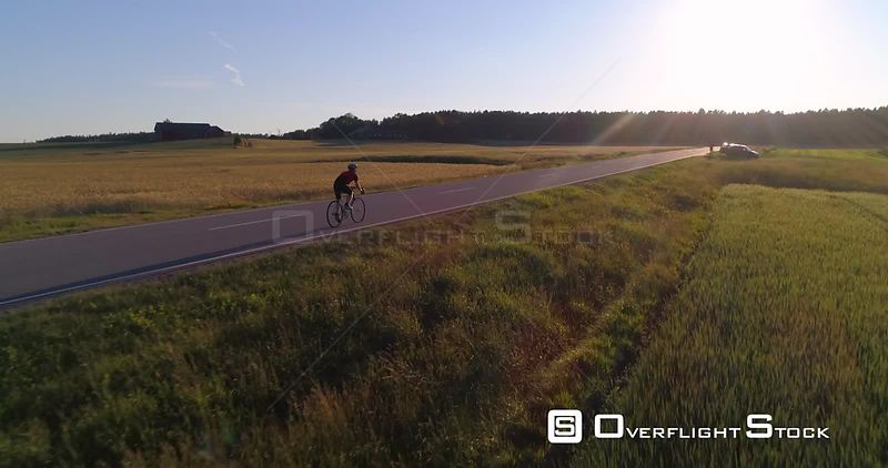 Man biking on the countryside, C4K aerial view closing in on a biker driving on a road, between wheat fields, on a sunny summer evening sunset, in Uusimaa, Finland
