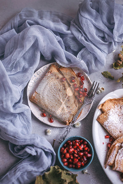 Spelt flour crepes with pomegranate seeds served for breakfast