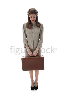A 1940's woman in a suit, Standing with a suitcase – shot from eye-level.