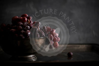 A footed, metal bowl filled with fresh red grapes on a patinated metal tray. Moody natural light with dark tones.