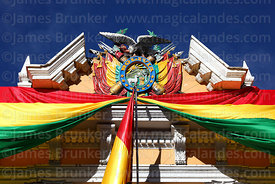 Bolivian national flag (tricolor) and coat of arms on facade of presidential palace for Independence Day, La Paz, Bolivia
