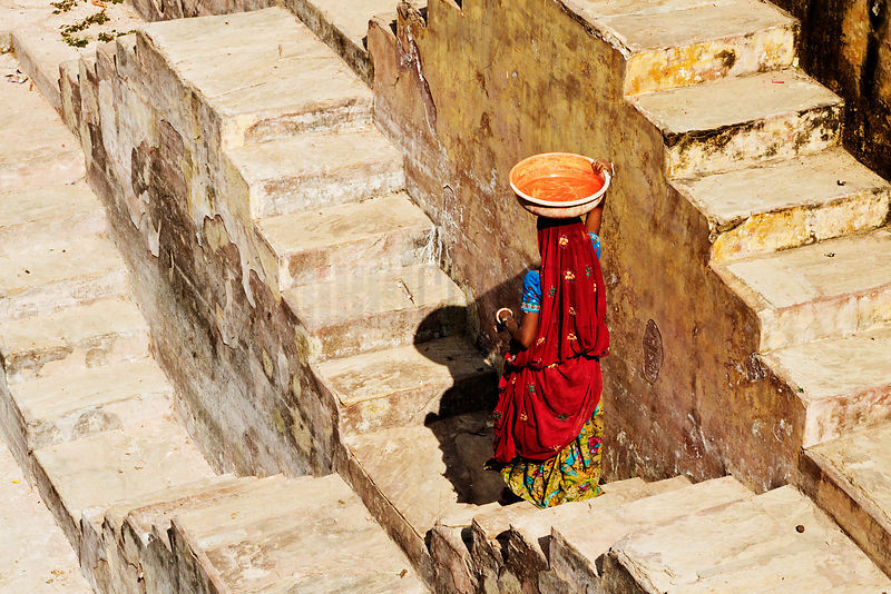 Female Laborer Carrying Load on Head inside Step Well