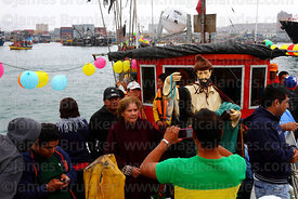 A woman has her photo taken with statue of St Peter on fishing boat during procession around port, St Peter and St Paul festival, Arica, Chile