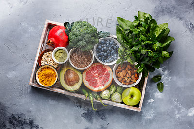 Healthy food clean eating selection in wooden box: fruit, vegetable, seeds, superfood, cereals, leaf vegetable on gray concrete background