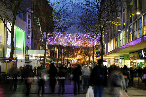 Birmingham City Centre. Christmas lights along New Street, the main shopping street, with shoppers.