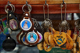 Virgen de Chaguaya and birth sign key rings for sale on stall outside Sanctuary, Chaguaya, Tarija Department, Bolivia