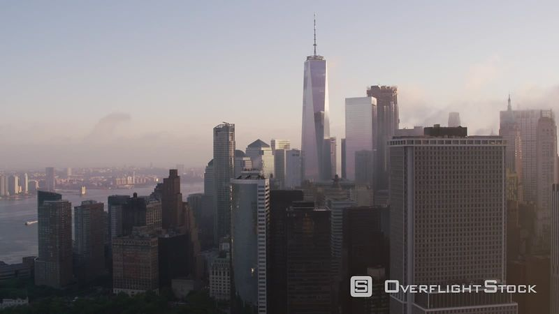 New York City Tracking by lower Manhattan buildings with low clouds and early morning sunshine.   Shot with Cineflex and RED EpicW Helium.