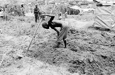 Burundi - Buhonga - Hutu peasant cultivates land in Buhonga Regroupment Camp watched by a soldier