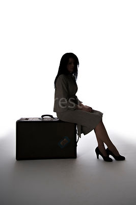 A silhouette of a 1940's woman sitting on a trunk / suitcase – shot from mid-level.