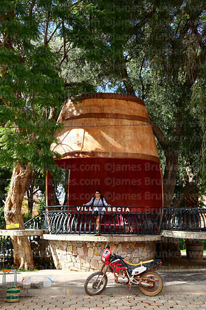 Tourist inside giant wooden wine barrel in village square, Villa Abecia, Chuquisaca Department, Bolivia