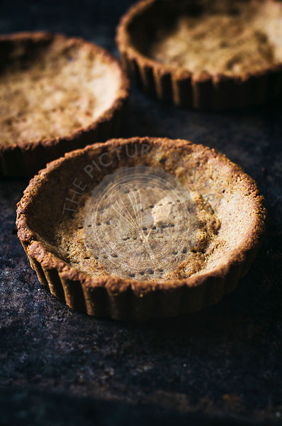 Small tart shells with fork marks on moody background