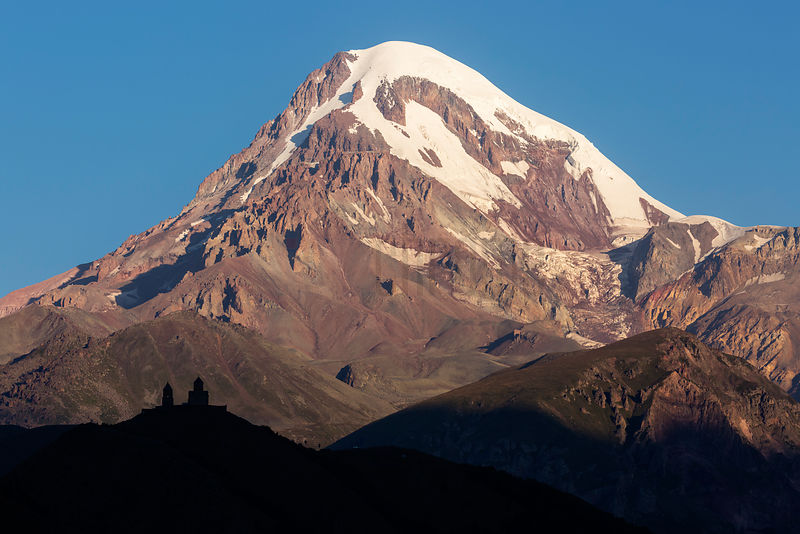 Elevated View of Mt Kazbegi and Gergeti Trinity Church Silhouetted in the Foreground