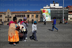 Aymara family walking past banner for visit of Pope Francis, Plaza San Francisco, La Paz, Bolivia