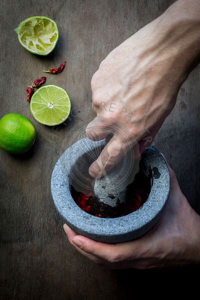 Man's hand with mortar and pestle preparing seasoning paste. Top view