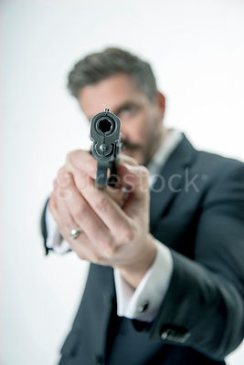 A mystery man pointing a gun – shot from mid level.