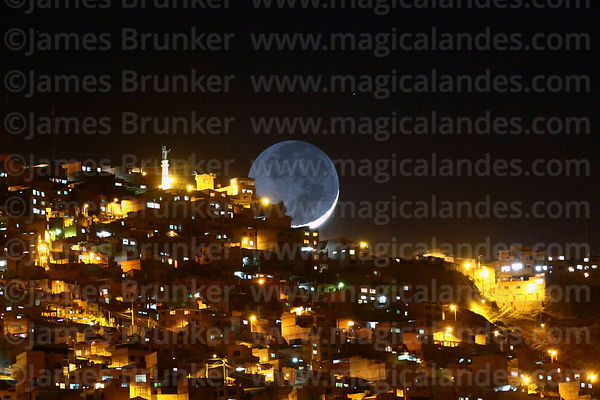 New moon setting over houses on hillside below La Ceja in El Alto, seen from La Paz, Bolivia