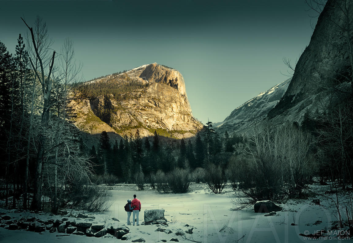 Couple by frozen lake looking at sunlit mountain