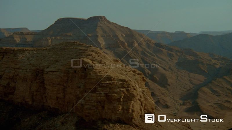 Aerial lens flare along dark weathered cliff face to end of rocky outcrop up and over top, wide shot sides of mountains curving dry riverbed in valley below Fish River Canyon Namibia