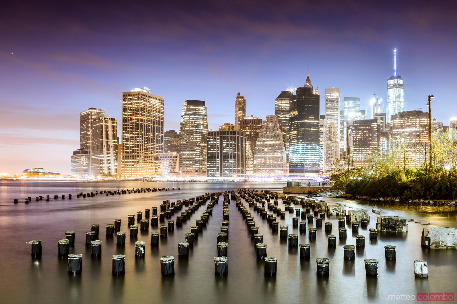 Lower Manhattan skyline reflected in the East river at dusk, New York, USA