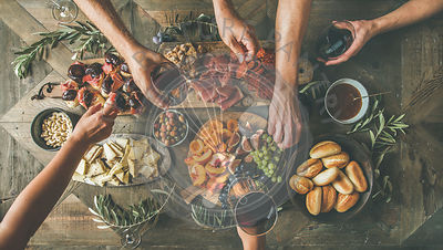 Top view of people having party, gathering, celebrating together at wooden rustic table set with different wine snacks