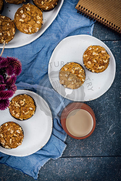 Banana nut muffins served on two white ceramic plates photographed from top view. A cup of coffee, flowers, a notebook accompany.