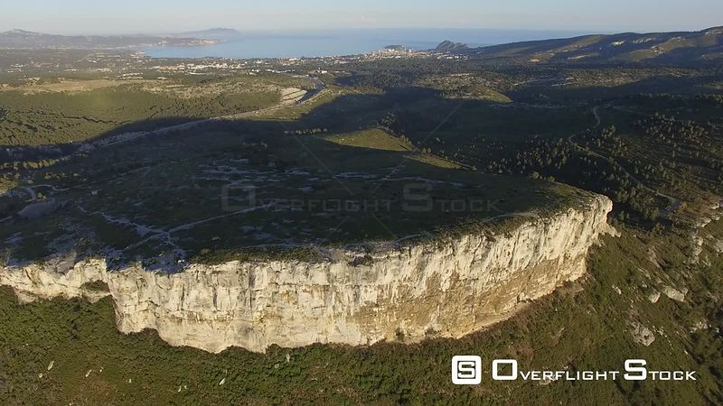 Aerial view of a rock overlooking Cassis village at sunset, filmed by drone, France