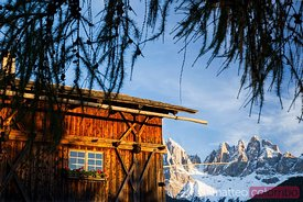 Traditional wooden hut and mountain peaks in the italian alps