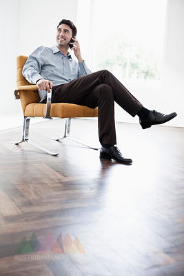 Businessman sitting in chair, using mobile phone