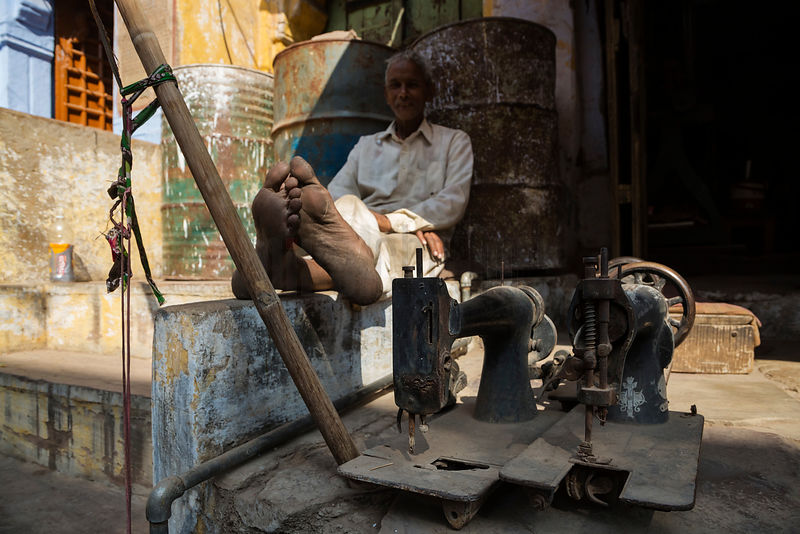 Portrait of a Sewing Machine Repair Man Sitting Outside his Shop