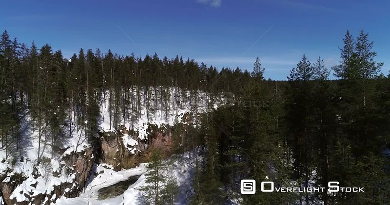 Finnish rapids, aerial rising drone view above kiutakongas rapid, revealing the oulanka national park, on a sunny winter day, in Kuusamo, PohjoisPohjanmaa, Finland